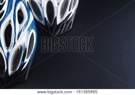 Two bicycle helmet closeup on a black background with copy space. Helmets male and female. Stylish sports background.