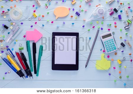 Office business education still life concept on blue wooden background. Top view of wooden desktop with e-book and bright colorful stationery items. Set of mock up e-book and stationery flat lay.