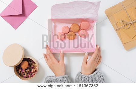 Sweet package. Flat lay of a box filled with delicious pink macaroons while being in hands of a pleasant young woman