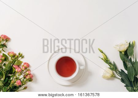 Fragrant drink. Flat lay of a porcelain cup filled with fragrant herbal tea while standing on the white surface between flowers