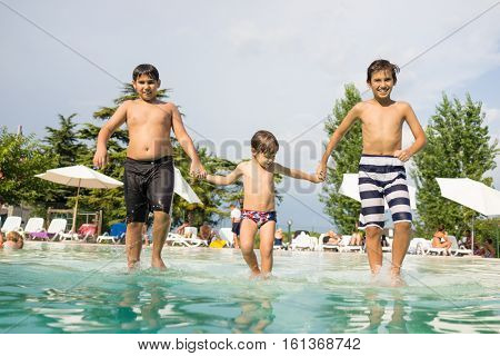 Happy time for kids of fun and enjoyment on summer swimming pool