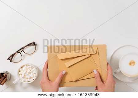 Sending letters. Pleasant young woman holding paper envelopes of different sizes while sending letters