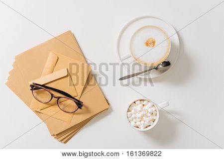 Prepared to be sent. Eyeglasses lying on the large pile of paper envelopes near the cup of coffee