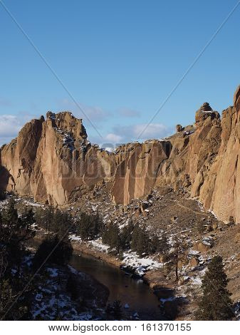 The rugged cliffs of Smith Rocks State Park in Central Oregon with fresh snow and the Crooked River below on a sunny winter day.