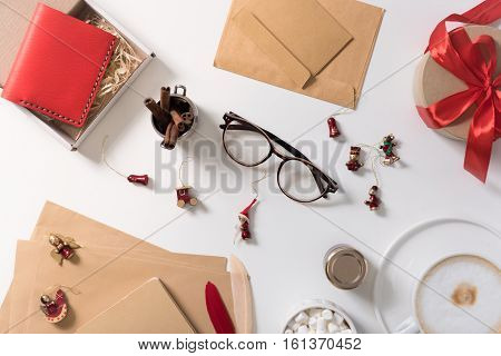 New Year celebration. Small Christmas tree decorations scattered on the white table while being prepared to be hung on the Christmas tree