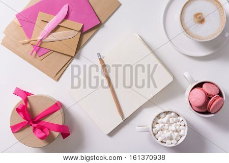Confession love letter. Open notebook lying on the table and being surrounded by delicious sweets while being used for writing a confession love letter