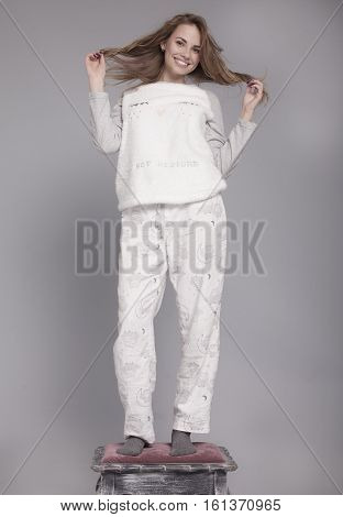 Happy teenage girl in funny pajamas on grey background studio. Funky teenager wearing Pajamas cartoon style