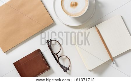 For better eyesight. Top view of eyeglasses lying between the business card holder and the open notebook