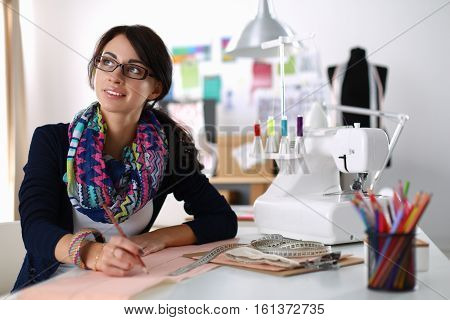 Dressmaker woman designing clothes pattern on paper .