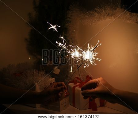 Christmas sparklers in darkness. New Year decorations on background.