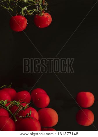 Tomatoes cherry in the water with dark background