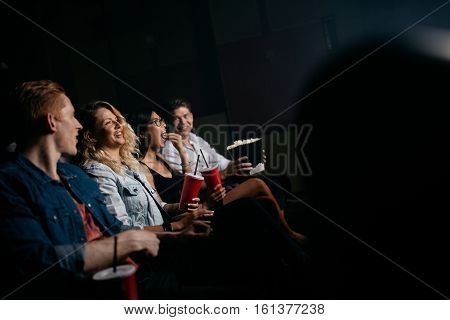 Group of friends sitting in multiplex movie theater with popcorn and drinks. Young people watching movie in cinema.