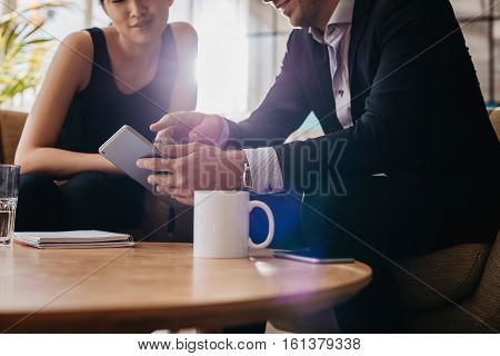 Cropped shot of businessman and businesswoman having a meeting in office lobby using digital tablet. Office workers using touchscreen computer.