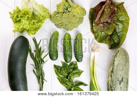 Green vegetables on white wooden background - broccoli zucchini lettuce estragon green onions chard basil cucumber Top view Flat lay