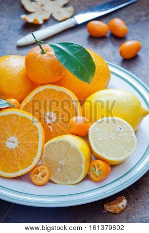 Oranges, tangerines, lemons and kumquats with green leaves on a plate on a dark wooden background