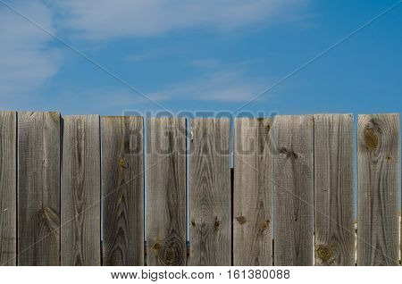 old wooden fence with gate on sky background with clouds