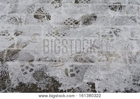 Wintertime - road covered with snow with traces of car tires and shoe prints