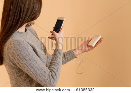Girl Take Photo Of Her Portable Charging On Yellow Background.modern Digital Gadget. Girls Hands Hol