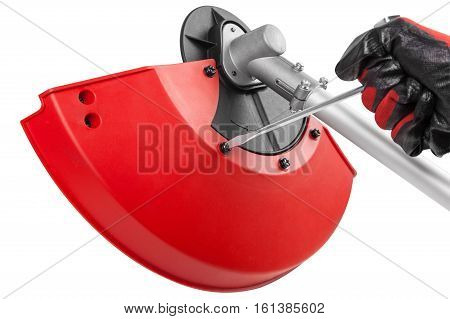 Photos hands working with screwdriver mounting protective cover on the new weed trimmer isolated on white background clipping path included