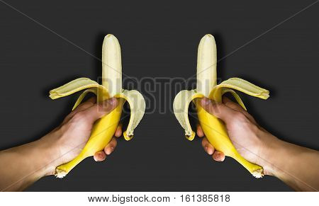 Two banana in his hand on a homogeneous background