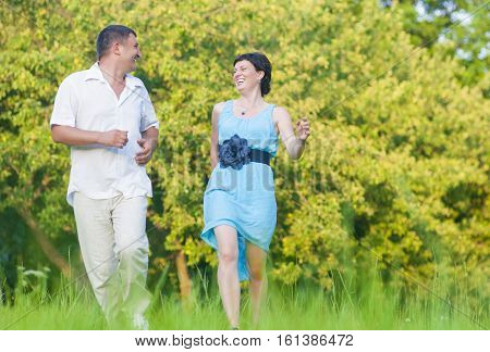 Couple Relationships Concepts and Ideas.Happy caucasian Couple Having Good Time Outdoors Running Together. Horizontal Image Orientation