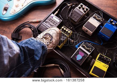 Stepping on a electric guitar audio processing effects on a studio or stage floor. Electric guitar and stomp box type effectors and cables on studio floor. Intentionally shot with low key tone.