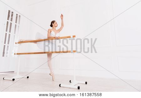Before performance. Serious attractive female standing straight on tiptoe putting right leg on the ballet bar holding left hand upwards