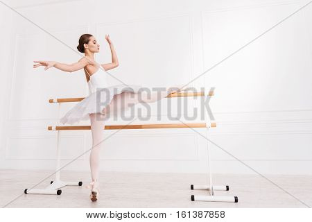 Lengthening out. Graceful young ballerina with bun on the head keeping arms in the air standing in semi position while stretching her leg