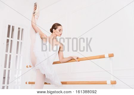 Do it with elegance. Amazing young ballerina with bun on the head wearing white leotard with tutu air standing in semi position while stretching her leg