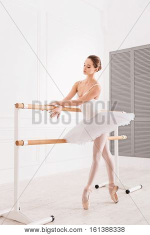 Elegant position. Full length picture of graceful female wearing leotard and white tutu looking at crossed hands while standing on tiptoes