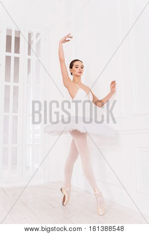Simplicity and elegance. Slim and slender pretty girl wearing points and tutu chest standing on tiptoes while keeping arms in the air during training