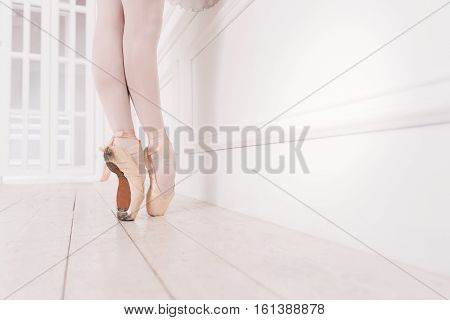 Shoes for ballet. Professional ballerina wearing white tights and points standing on tiptoes while posing in dance studio