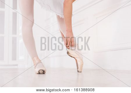 Points for professionals. Professional dancer wearing white tights and points standing on tiptoes while posing in dance studio