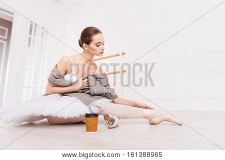 Have a break. Professional young ballerina holding grey shawl on her shoulders looking at her right leg before drinking tea