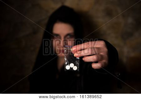 Drug addict demonstrating wheels, tablets with substance. Drug addict isolated on brick wall background on street.