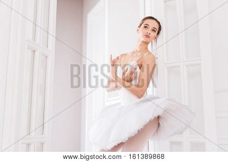 Follow your dreams. Graceful young brunette crossing both arms on the chest looking sideways while standing in the doorway
