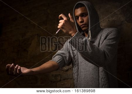 Drugs concept. Disease concept. Drug addict man with syringe using drugs. Drug addict holding syringe with drugs in front of him.