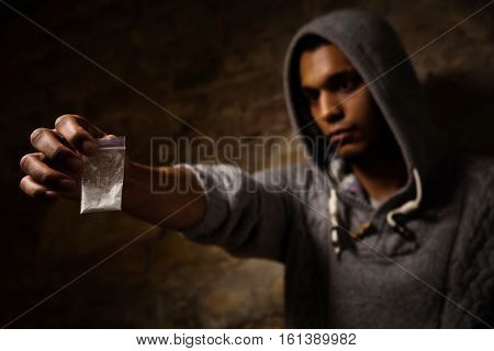 Drug addict showing narcotics and holding them in front of him. Drug addict varies whether to take drugs in form of white powder.