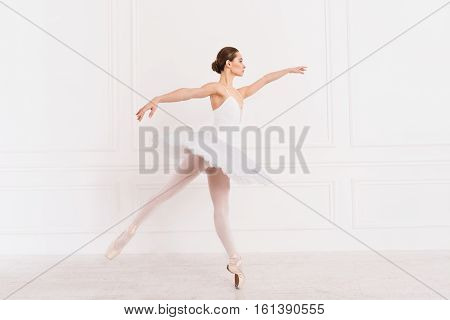 Improve it. Graceful young woman wearing white leotard with tutu looking sideways keeping arms straight in the air