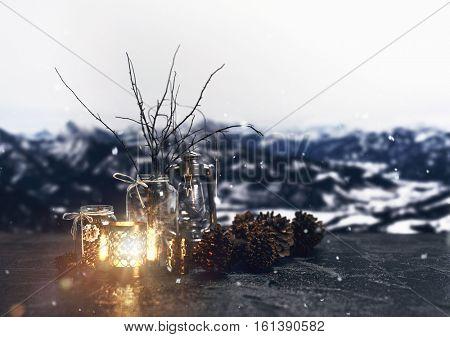 Christmas winter decoration background with candles, fir cones, historic oil lamp and wooden sprays in a glass flower vase standing on a black slate in front of snowy mountain range. 3d Rendering.