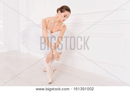 Try this pose. Elegant brunette wearing white leotard with tutu while standing in ballet position holding both hands crossed on knees