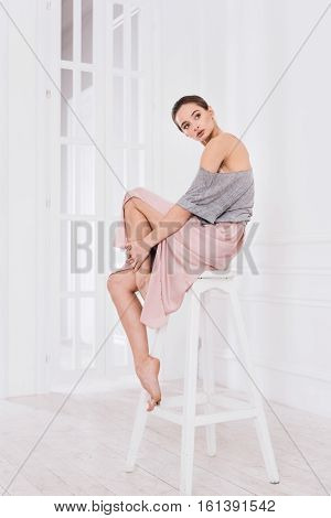 Just relax. Graceful woman wearing grey top over pink dress while sitting on the chair in studio putting hands on left leg