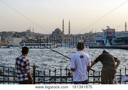 Istanbul Turkey - October 2 2012: Istanbul Landscape on the opposite shore New Mosque And fishermen on the shore. The Yeni Cami ; originally named the Valide Sultan Mosque and later New Valide Sultan Mosque after its partial reconstruction and completion