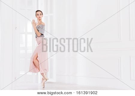 Everything will be great. Majestic pretty ballerina putting left hand on the door looking sideways while standing on tiptoes