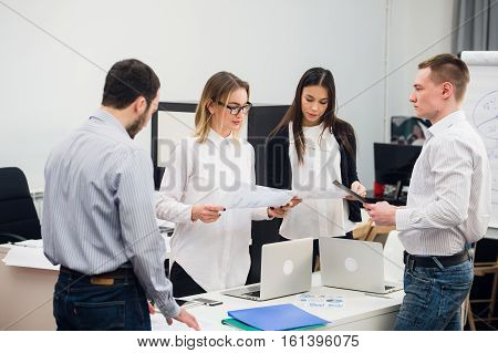 Four young business people working as a team gathered around a laptop computer in an open plan modern office.