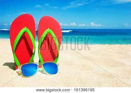 Holidays Background. Beach sandals on the sandy coast