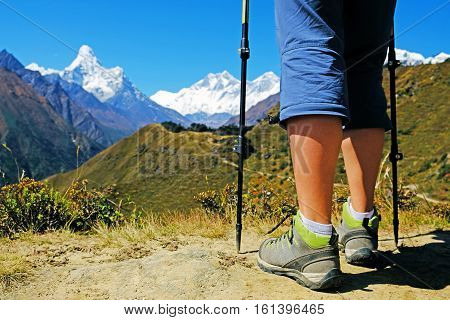 Woman hiker legs stand on mountain peak. Success freedom and happiness achievement in mountains. Active sport concept.