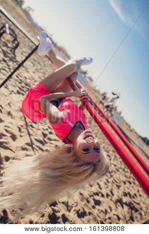 Beautiful female hanging upside down at beach