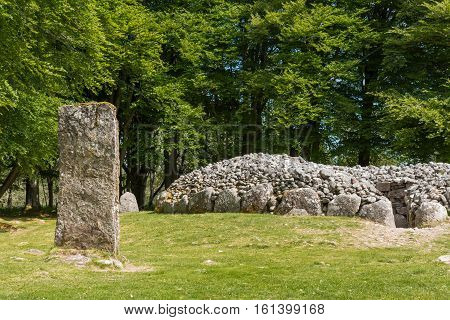 Inverness Scotland - June 2 2012: One menhir of the stone circle and grave site heap of gray stones at prehistoric Clava Cairns. Surrounded by green trees and grassy field.