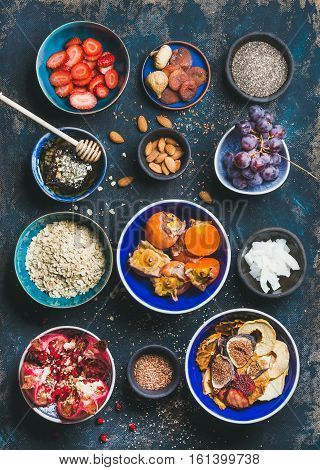 Ingredients for healthy breakfast over dark blue background, top view. Fresh and dried fruit, chia seeds, oatmeal, nuts, honey. Clean eating, vegan, vegetarian, healthy food, detox and dieting concept
